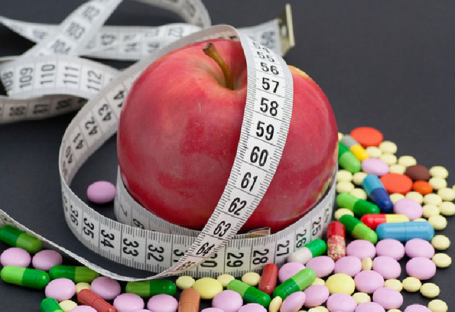 diet pills, apple, and measuring tape