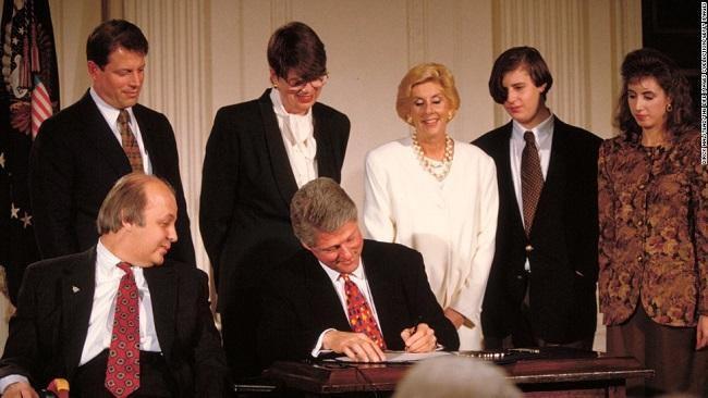 Jim Brady sits by President Bill Clinton as he signs the Brady Bill into law